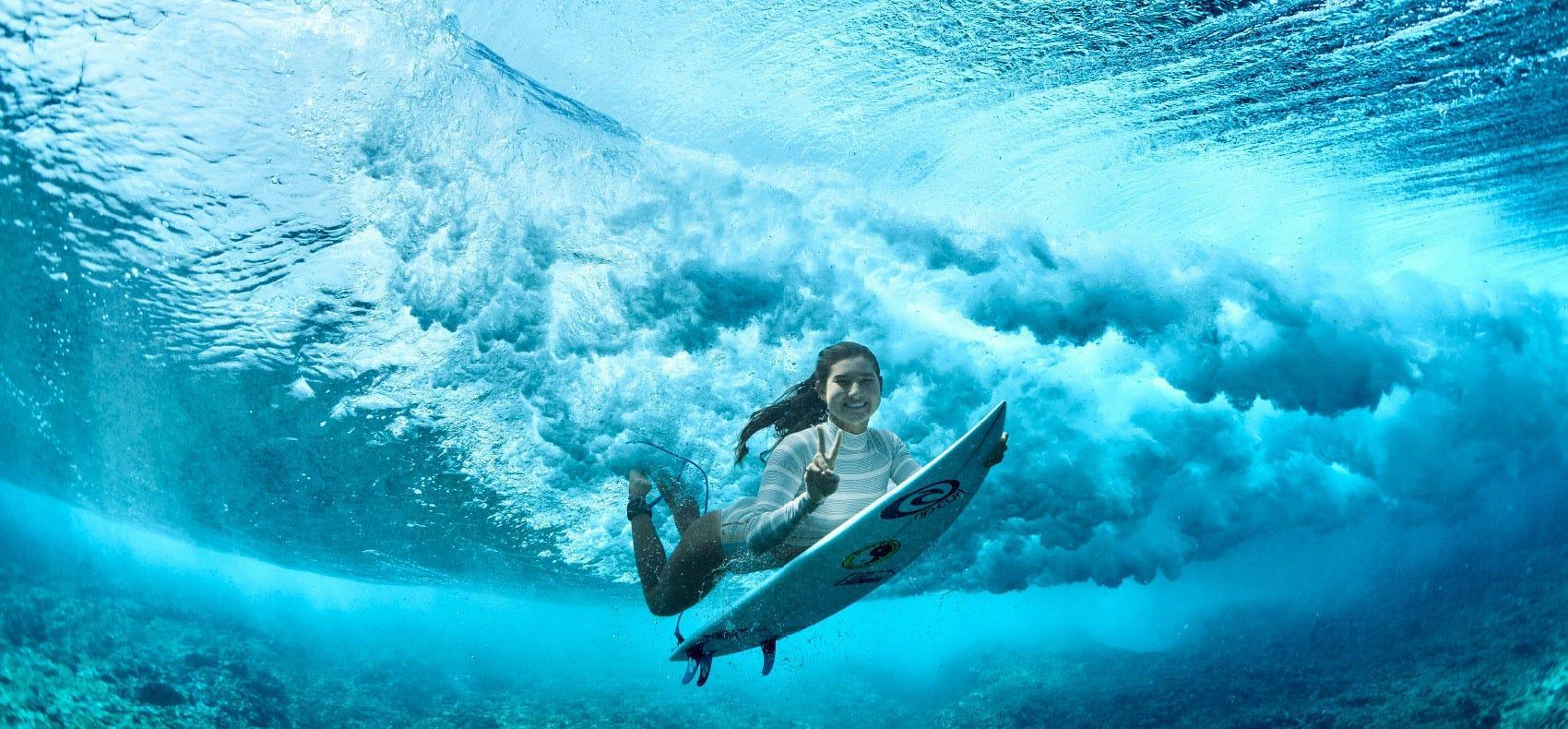 Brisa Hennessy duck-diving under a wave in Fiji